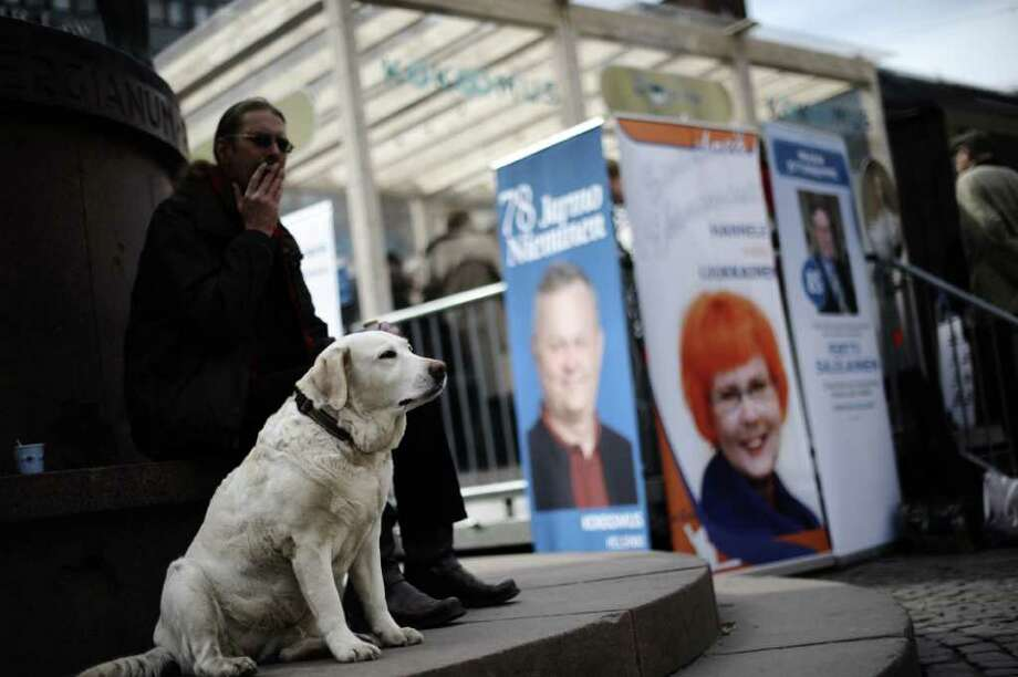 A Finnish man smokes a cigar as he sits with his dog near the campaign office of the National coalition, a liberal conservative political party in Finland, in Helsinki on April 14, 2011 ahead of the April 17 elections. Photo: AFP/Getty Images
