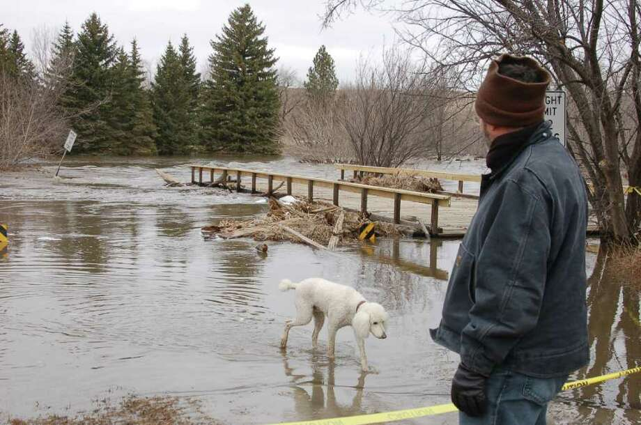 Robert Kibler and his dog, Alfie, survey the flooded Des Lacs River in Burlington, N.D., on Wednesday, April 13, 2011. Kibler and his wife, Alex Duefel, left their home on Tuesday but returned Wednesday to move their collection of 7,000 books to a main floor. Photo: AP