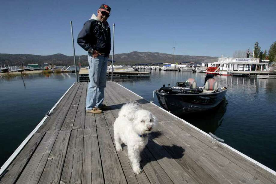 Bob Miller and his dog Muttsey return from fishing to a boat launch ramp on Tuesday, April 12, 2011 at Big Bear Lake, Calif.  Record rainfall has filled Big Bear Lake to the brim this winter, forcing officials in the San Bernardino Mountain community to release water from the lake for the first time in 15 years. Photo: AP