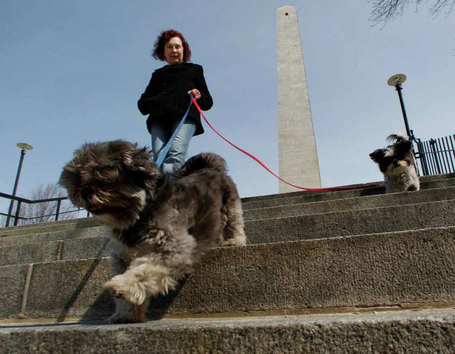 Mary Moore, of the Charlestown neighborhood of Boston, walks her two dogs Leo, left, and Lola, right, around the National Park Service Bunker Hill monument, which is part of the Boston National Historic Park, in Boston, Saturday, April 9, 2011.  A last-minute budget deal forged with tough bargaining averted an embarrassing U.S. government shutdown, cut billions in spending and provided the first major test of the divided government that voters ushered in five months ago. Photo: AP