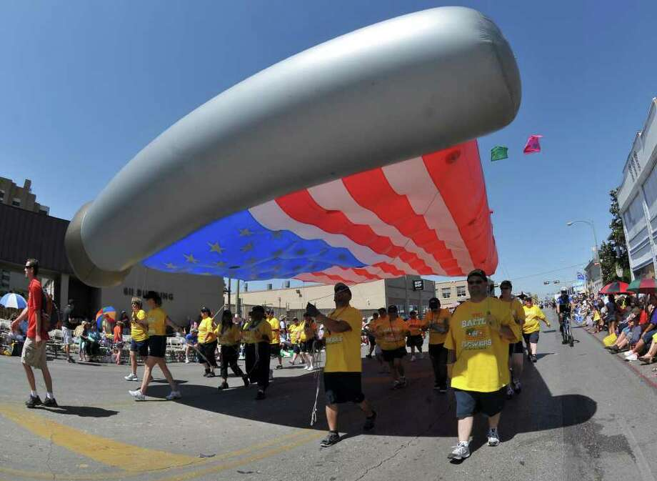 SLUG: BOF2011RJ-No Photo Request number-April 15, 2011-San Antonio, Texas--- A large, inflated American flag is guided along Broadway St. during the Battle of Flowers Parade 4/15 Photo by Robin Jerstad/Special to the Express-News Photo: Photo By Robin Jerstad/Special To The Express-News / Robert Jerstad