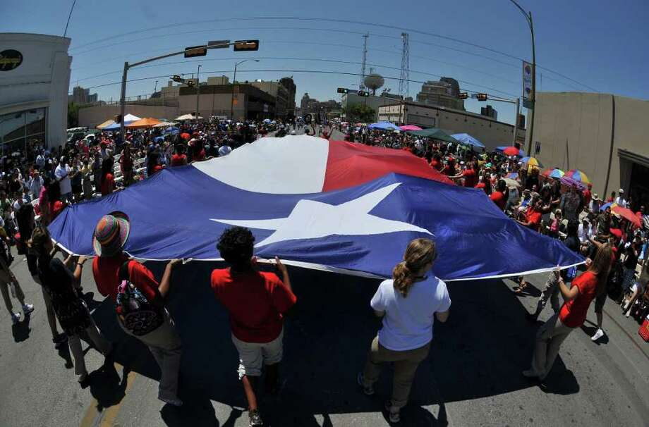 SLUG: BOF2011RJ-No Photo Request number-April 15, 2011-San Antonio, Texas---Girls Scouts manuever a huge Texas flag along Broadway St. during the Battle of Flowers parade 4/15.  Photo by Robin Jerstad/Special to the Express-News Photo: Photo By Robin Jerstad/Special To The Express-News / Robin Jerstad