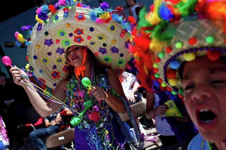 "metro - Karen Gonzales, left, and her grandson, Jonathan De Leon, 8, yell ""show us your shoes"" during the Battle of Flowers Parade in San Antonio on Friday, April 15, 2011. LISA KRANTZ/lkrantz@express-news.net Photo: LISA KRANTZ, SAN ANTONIO EXPRESS-NEWS / SAN ANTONIO EXPRESS-NEWS"