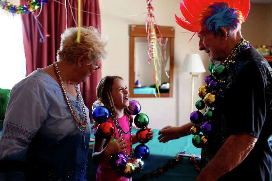 "metro - Weldon Albertson, 82, who had the same room at the Travelodge on Broadway overlooking the parade route for 43 years for the parade weekend, tries out his biggest beads on Alexandria Perez, 7, with her grandmother, Frances ""Andie"" Perez, during the Battle of Flowers Parade in San Antonio on Friday, April 15, 2011. LISA KRANTZ/lkrantz@express-news.net Photo: LISA KRANTZ, SAN ANTONIO EXPRESS-NEWS / SAN ANTONIO EXPRESS-NEWS"