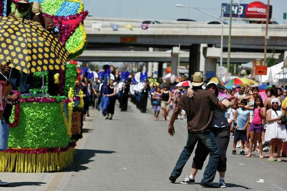 San Antonio Zulu member dances to the music from the Zulu float with a spectator during the Battle of Flowers Parade in San Antonio on Friday, April 15, 2011. Bria Webb/Special to the Express-News Photo: BRIA WEBB, SAN ANTONIO EXPRESS-NEWS
