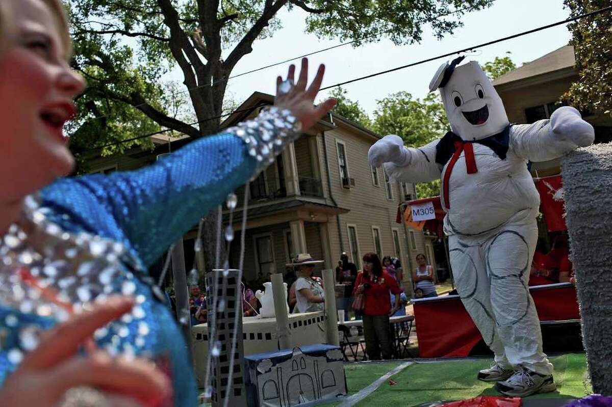Terrie Sharp, left, waves to the Armando Garza, dressed as the Stay Puft Marshmallow Man from Ghostbusters, riding on the South Texas Memorials float during the King William Parade in San Antonio on Saturday, April 16, 2011. LISA KRANTZ/lkrantz@express-news.net