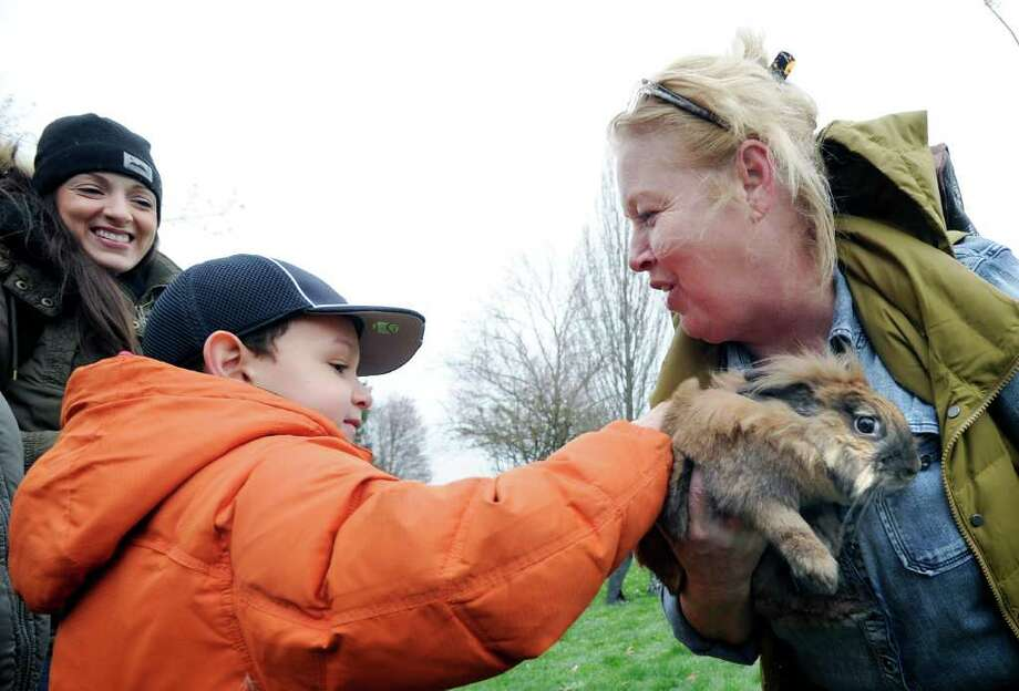 Julian Mendez, 6, of Norwalk, pets a Lionhead rabbitt held by Jane Reilly, president of the Greenwich Lions Club during the Greenwich Lions & ShopRite Annual Egg Hunt at Roger Sherman Baldwin Park, Greenwich, Saturday morning, April 16, 2011. Photo: Bob Luckey / Greenwich Time
