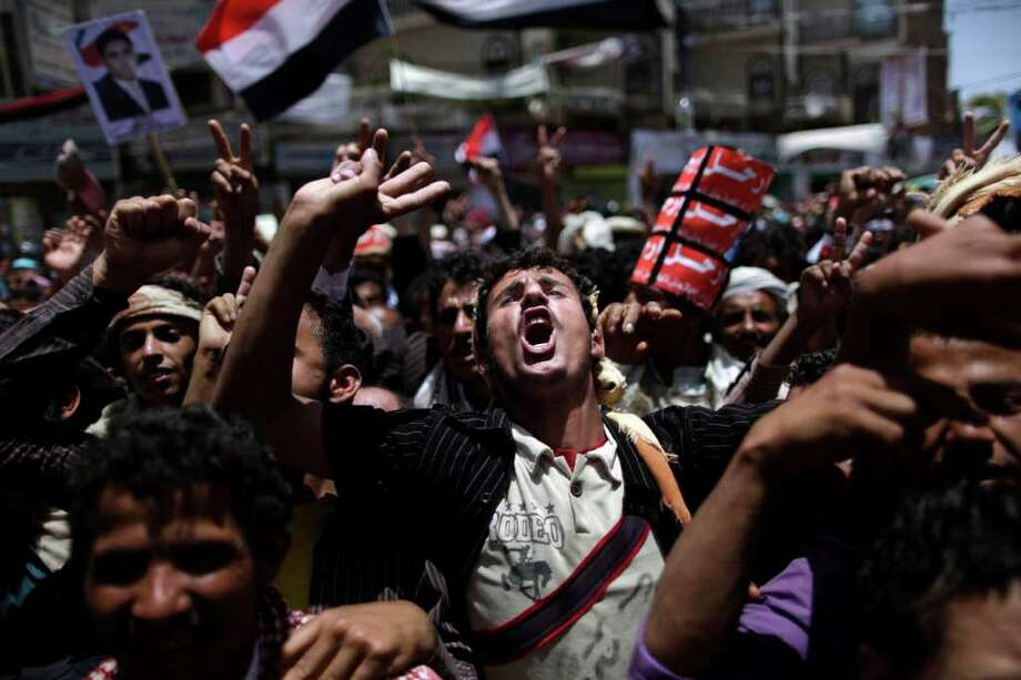 An anti-government protestor, center,  shouts slogans during a demonstration demanding the resignation of Yemeni President Ali Abdullah Saleh, in Sanaa, Yemen, Saturday, April 16, 2011. Dozens of chiefs from Yemen's two largest and most powerful tribes called on the president to immediately step down and strip his son of control over security forces, as rival crowds of protesters took to the streets Friday. (AP Photo/Muhammed Muheisen) Photo: Muhammed Muheisen / AP