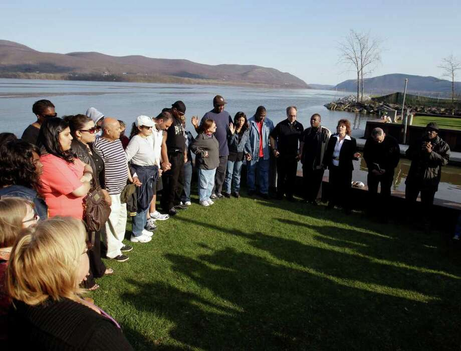 FILE - In this Thursday, April 14, 2011 file photo, people attend a vigil at the boat ramp where Lashanda Armstrong drove her minivan into the Hudson River on Tuesday night killing herself and three of her children, in Newburgh, N.Y. Mothers kill their children in this country much more often than most people would realize by simply reading the headlines; by conservative estimates it happens every few days, at least 100 times a year. Experts say more mothers kill their children under 5 years of age than fathers. And, some say, our reluctance as a society to believe mothers would be capable of killing their offspring is hindering our ability to recognize warning signs, intervene and prevent more tragedies. (AP Photo/Mike Groll, File) Photo: Mike Groll