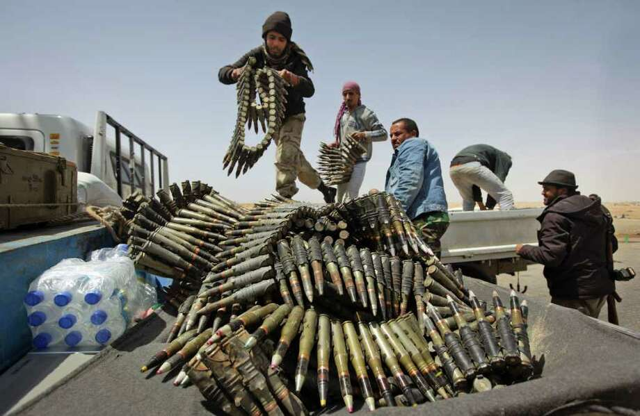 Libyan rebel fighters load a truck with ammunition on the outskirts of Ajdabiya, Libya, Saturday, April 16, 2011. (AP Photo/Ben Curtis) Photo: Ben Curtis / AP