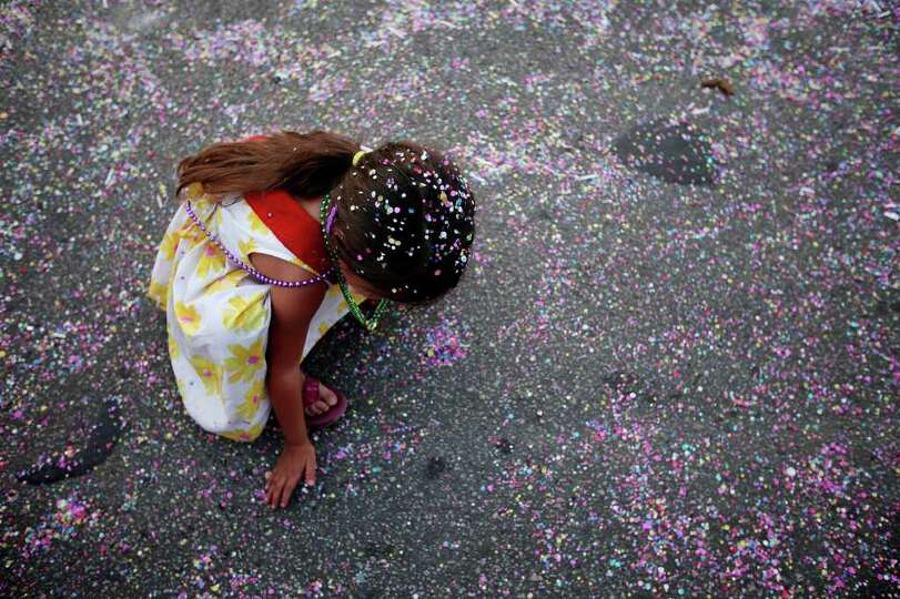 FOR METRO - Maryn Vasquez, 4,  gathers confetti  during the Fiesta Flambeau Parade Saturday April 16