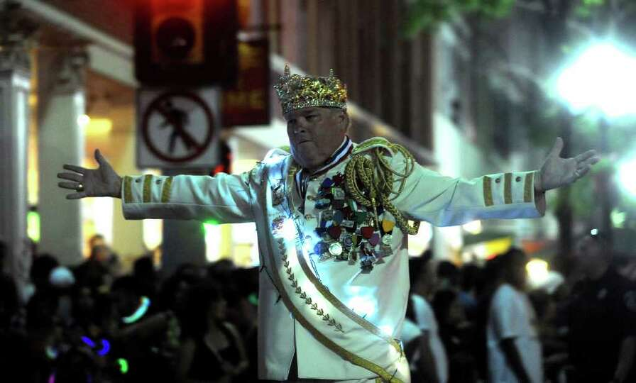 Bill Drain, El Ray Feo 2011, acknowledges the Fiesta Flambeau Parade crowd as he marches on Saturday