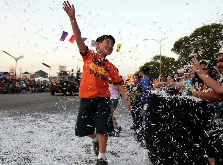 FOR METRO - Dylan Fernandez, 8, throws confetti  during the Fiesta Flambeau Parade Saturday April 16