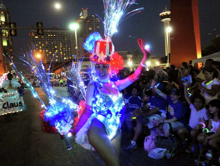 Tina Zavala lights up the night as she participates in the Fiesta Flambeau Parade on Saturday, April