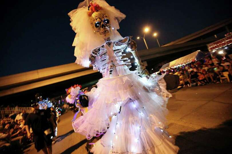 FOR METRO - A member of Las Monas San Antonio takes part in the Fiesta Flambeau Parade Saturday Apri