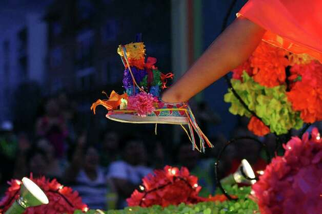 A Fiesta queen shows her shoes during the Fiesta Flambeau Parade last  year. Now it's your turn. Photo: File Photo, San Antonio Express-News / SAN ANTONIO EXPRESS-NEWS (NFS)