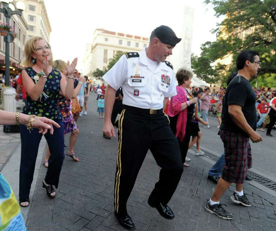 "Maj. Gen. Perry Wiggins deputy commanding general, U.S. Army North at Fort Sam Houston, dances the ""electric slide"" before the Fiesta Flambeau Parade on Saturday, April 16, 2011. BILLY CALZADA / gcalzada@express-news.net Photo: BILLY CALZADA, Express-News / gcalzada@express-news.net"