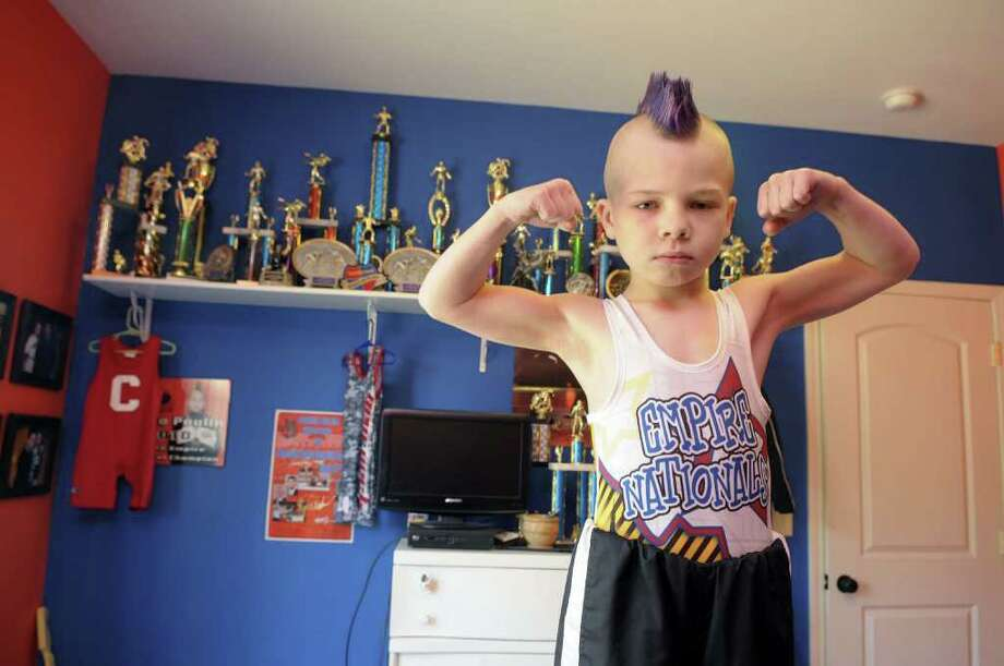 Wrestler Stevo Poulin, 8,  in his bedroom with just some of the trophies he has won competing, poses in his bedroom at his home on Thursday morning, April 14, 2011 in Schuylerville.  Stevo has become an Internet sensation after his family posted some of his wrestling match higlights on YouTube.   (Paul Buckowski / Times Union) Photo: Paul Buckowski  / 00012754A