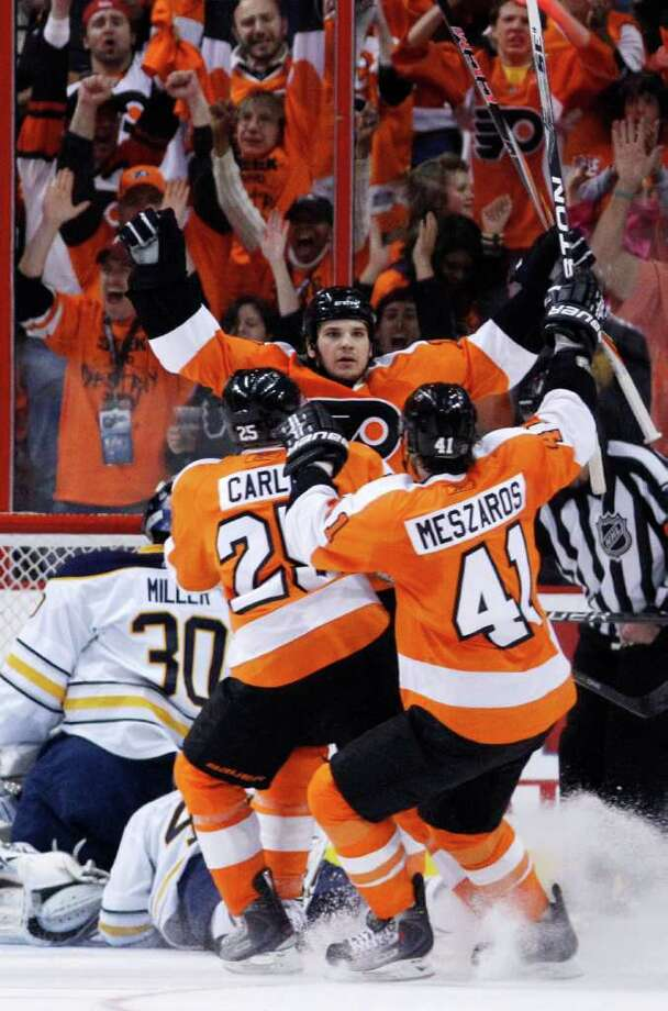 Philadelphia Flyers' Daniel Carcillo, center, and Matt Carle, second from left, and Andrej Meszaros, right, of Slovakia, celebrate after Carcillo's goal against Buffalo Sabres goalie Ryan Miller, left,  during the first period in Game 2 of a first-round NHL Stanley Cup playoffs hockey series, Saturday, April 16, 2011, in Philadelphia. (AP Photo/Matt Slocum) Photo: Matt Slocum