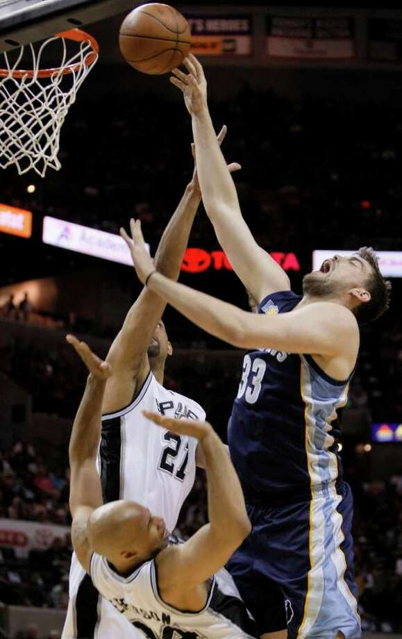Memphis Grizzlies' Marc Gasol, right, of Spain, shoots over San Antonio Spurs' Tim Duncan, center, and Richard Jefferson during the first half of an NBA playoff basketball game on Sunday, April 17, 2011, in San Antonio. Photo: AP