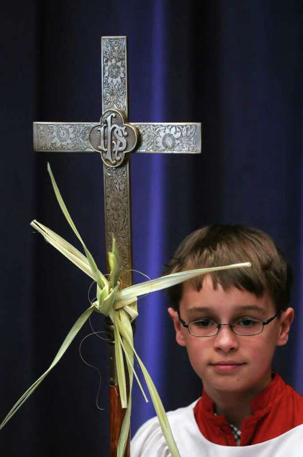 Ethan Knapp, 12, an acolyte at St. John's Evangelical Lutheran Church in Albany, holds a cross with a palm wrapped around it, prior to the start of a bilingual ceremony to bless palms at the church for Palm Sunday, on Sunday April 17, 2011 in Albany, NY. ( Philip Kamrass / Times Union ) Photo: Philip Kamrass