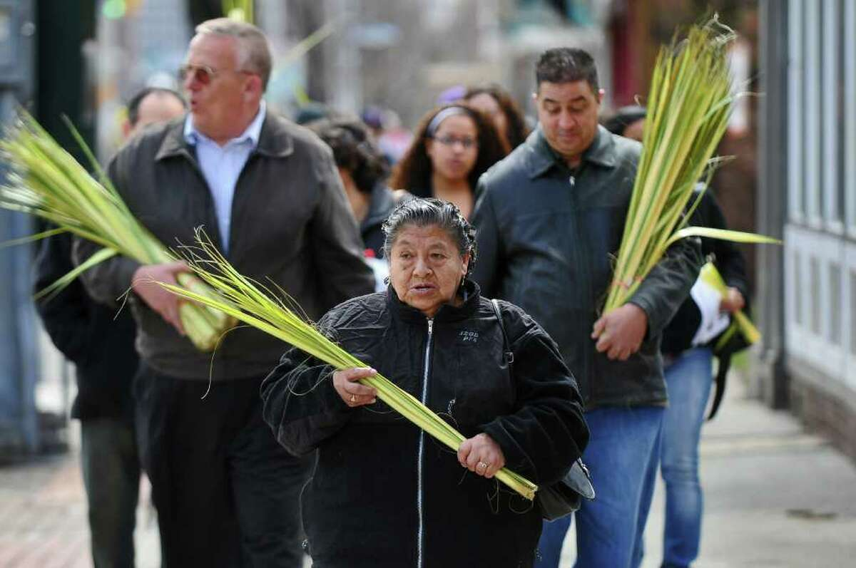 Maria Quispen of Albany returns in a procession along Central Avenue to the Shrine Church of Our Lady of the Americas while holding palms with other church members following a bilingual palm blessing ceremony with members of the nearby St. John's Evangelical Lutheran Church on Palm Sunday, April 17, 2011, in Albany, NY. Members of Todos Los Hijos de Dios, of Amsterdam, were also there. ( Philip Kamrass / Times Union )