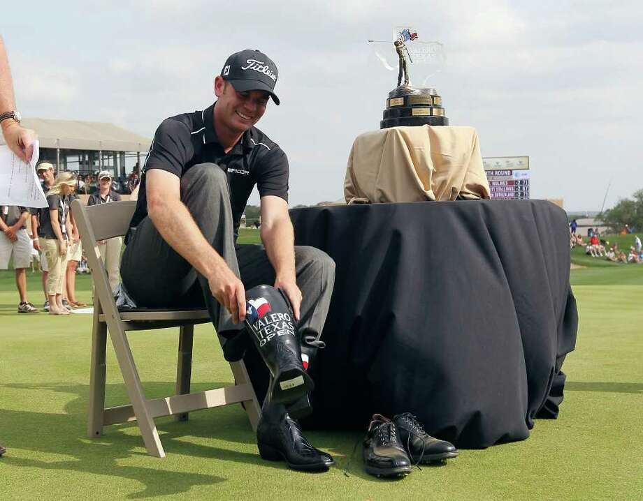Brendan Steele, the 2011 Valero Texas Open champion, slips on the traditional pair of cowboy boots after winning his first PGA Tour title on Sunday at TPC San Antonio. Photo: KIN MAN HUI, Kin Man Hui/kmhui@express-news.net / San Antonio Express-News