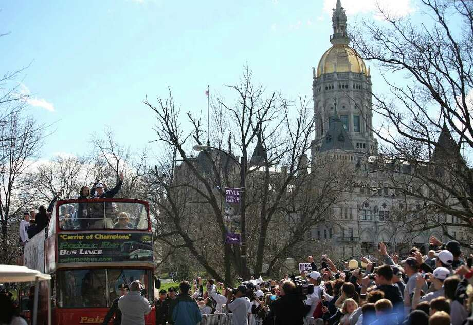 UConn men's basketball coach Jim Calhoun and his players wave to fans from atop a double decker bus as the team's NCAA Championship victory parade makes its way down Trinity Street in Hartford on Sunday, April 17, 2011. Photo: Brian A. Pounds / Connecticut Post
