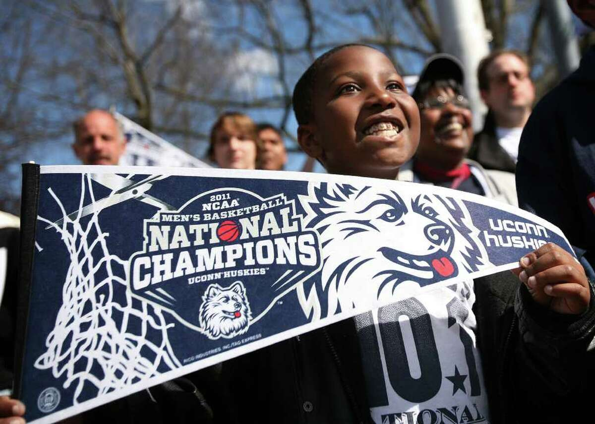 Carter Newman, 9 of Cromwell, beams up at the players during the UConn men's basketball NCAA Championship victory parade in Hartford on Sunday, April 17, 2011.