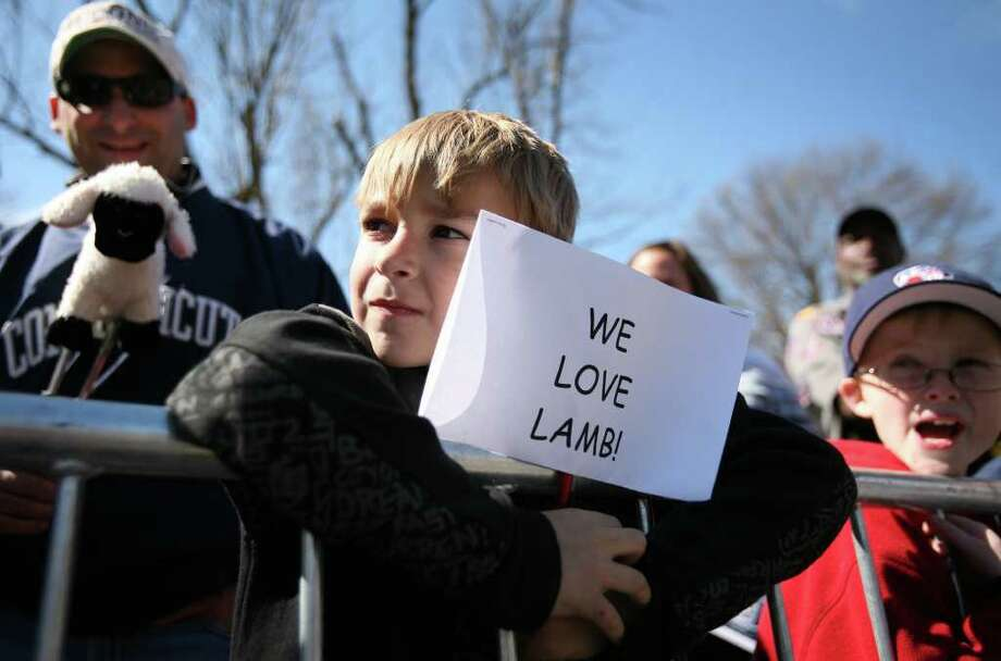 Jake Marcella, 6, and his father Ted of Windsor Locks, wait for the players bus, and their favorite player Jeremy Lamb, during the UConn men's basketball NCAA Championship victory parade in Hartford on Sunday, April 17, 2011. Photo: Brian A. Pounds / Connecticut Post