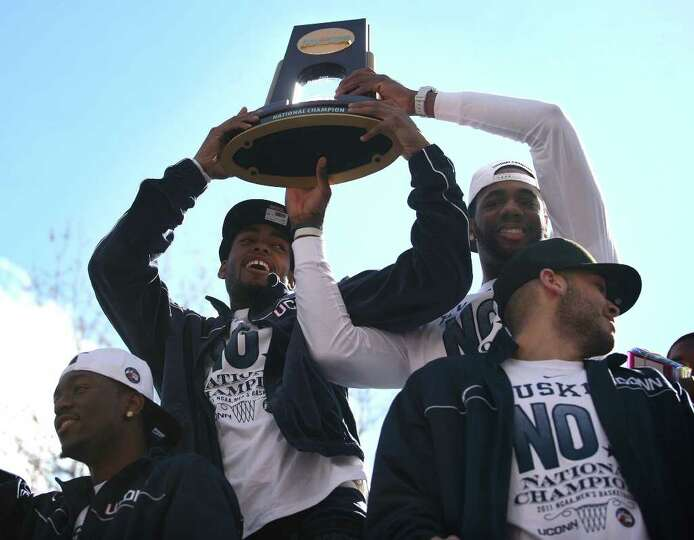 UConn players Jamal Coombs-McDaniel, second from left, and Alex Oriakhi, hoist the NCAA Championship