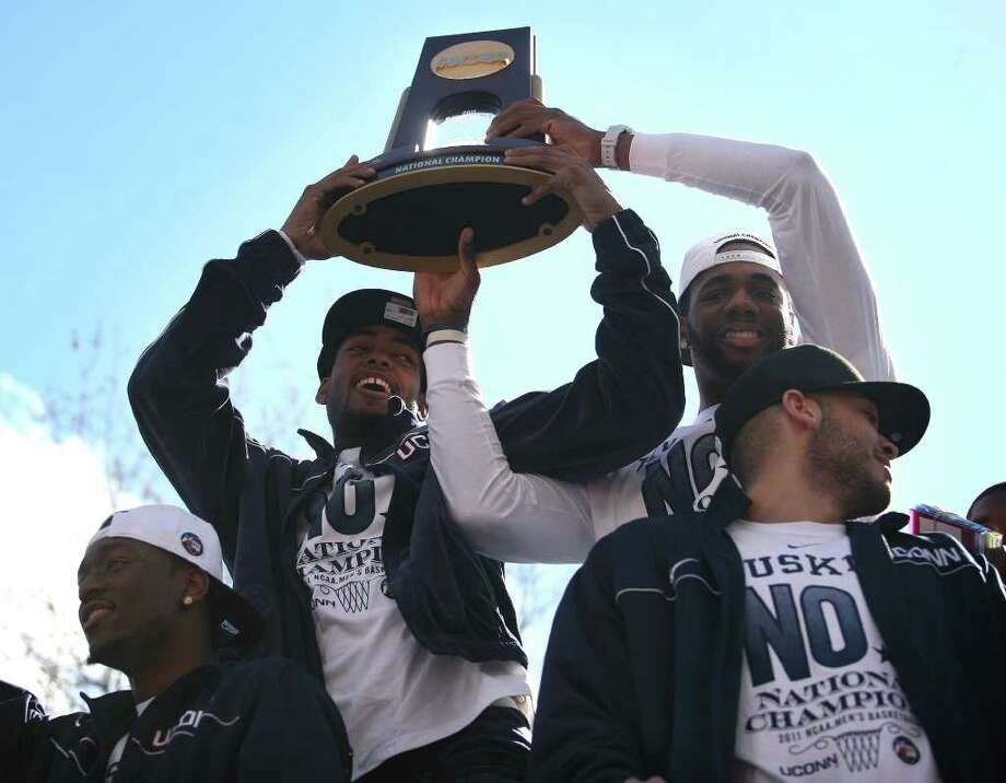 UConn players Jamal Coombs-McDaniel, second from left, and Alex Oriakhi, hoist the NCAA Championship trophy during the victory parade in Hartford on Sunday, April 17, 2011. At left is UConn star player Kemba Walker. Photo: Brian A. Pounds / Connecticut Post