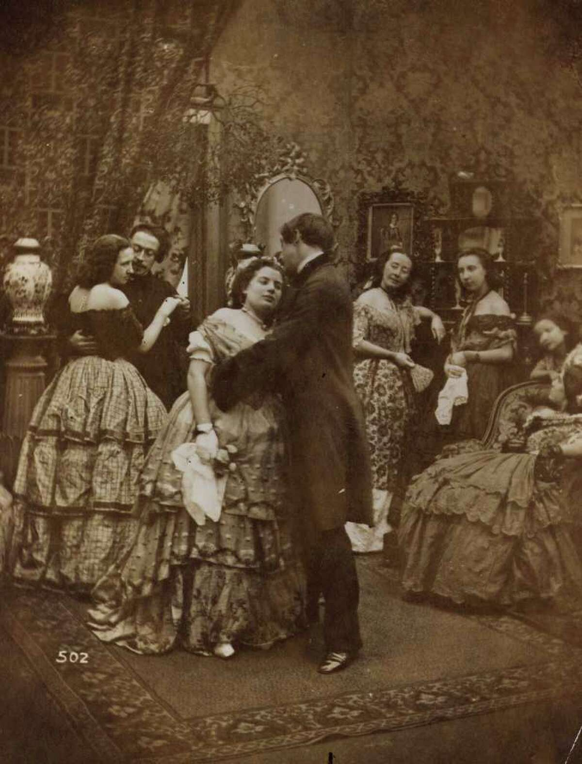 circa 1880: Couples dancing and kissing under the mistledoe at a soiree in Victorian times.