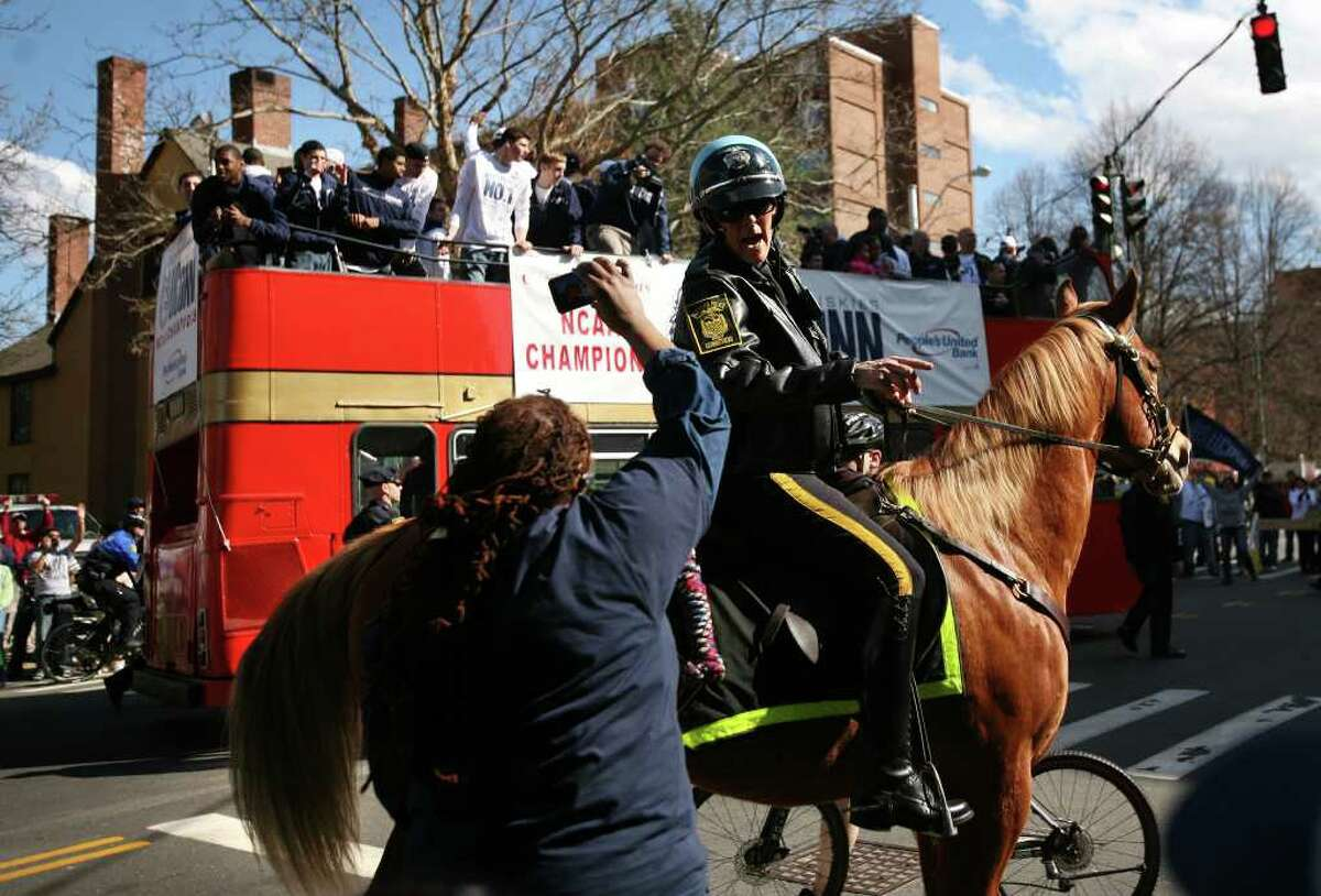 A mounted police officer works to keep a fan back during the UConn men's basketball NCAA Championship victory parade in Hartford on Sunday, April 17, 2011.