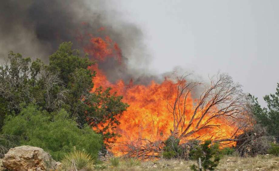 A wildfire flairs up on the west side of Possum Kingdom Lake, Texas, Saturday, April 16, 2011.  (AP Photo/LM Otero) Photo: LM Otero
