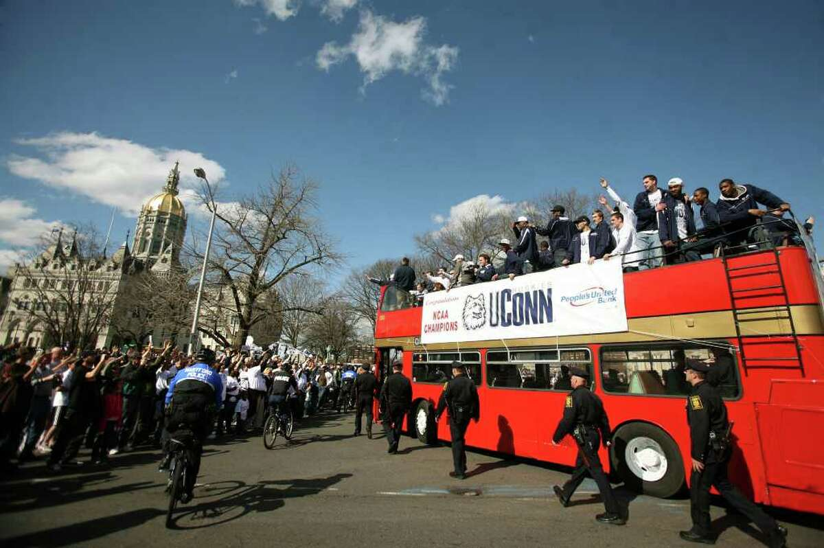 The UConn men's basketball team is welcomed by thousands of screaming fans as they ride atop a double decker bus in a victory parade in Hartford which began and ended at the State Capitol building on Sunday, April 17, 2011.