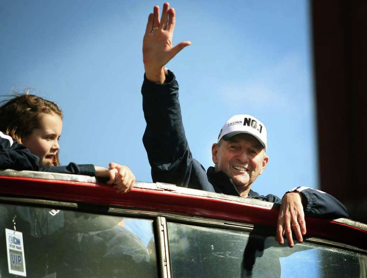 Accompanied by three of his granddaughters, UConn men's basketball coach Jim Calhoun waves to fans during his team's NCAA Championship victory parade in Hartford on Sunday, April 17, 2011.