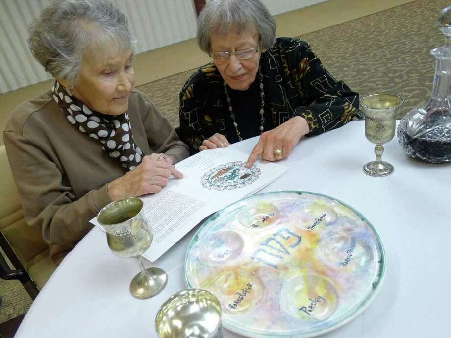 Sisters Gertrude Wallis and  Ruth Tenzer, residence of Daughters of Sarah Senior Community, reading from the new large-print ?A Family Haggadah,? written by Shoshana Silberman and illustrated by Katherine Janus Kahn in Albany Friday  April 15, 2011. ( Michael P. Farrell/Times Union ) Photo: Michael P. Farrell / 00012787A