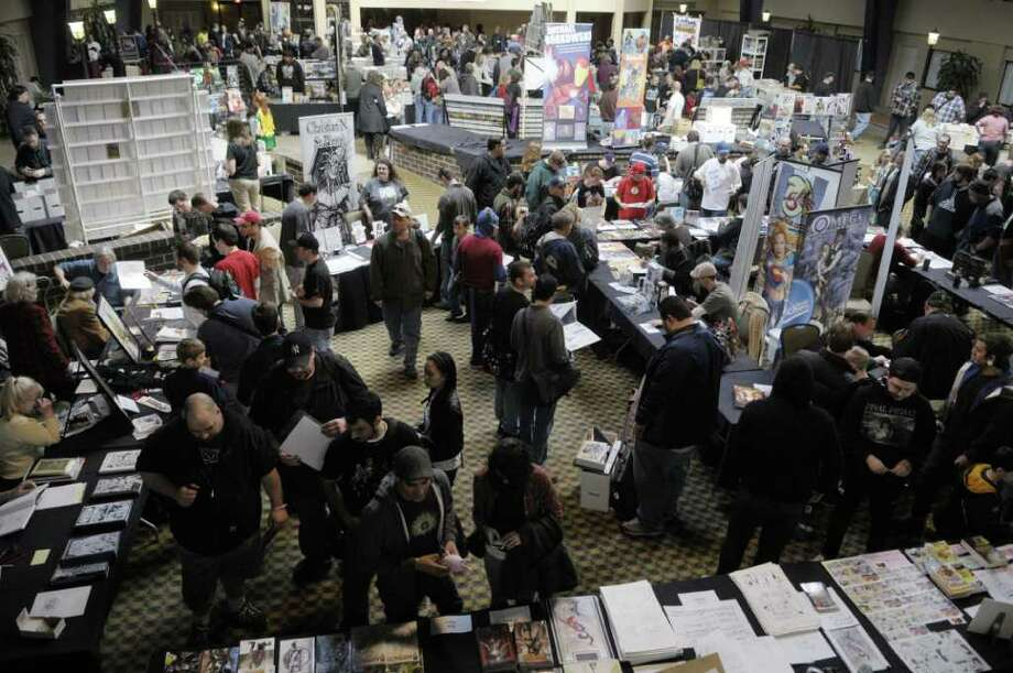 Comic fans look over comics and artowork during Albany Comic Con on Sunday morning, April 17, 2011 at the Holiday Inn in Colonie.  This is the fifth year of Comic Con, started by John Belskis who owns the comic shop, Excellent Adventures in Ballston Spa.  Area comic shops are involved with helping put on the show.  Comic Con brings in between 600 to 700 comic fans each year.  This years show included a silent auction of original drawings or comic pages with the proceeds going to Catholic Charities to be used for Japanese earthquake relief.   (Paul Buckowski / Times Union) Photo: Paul Buckowski / 00012779A