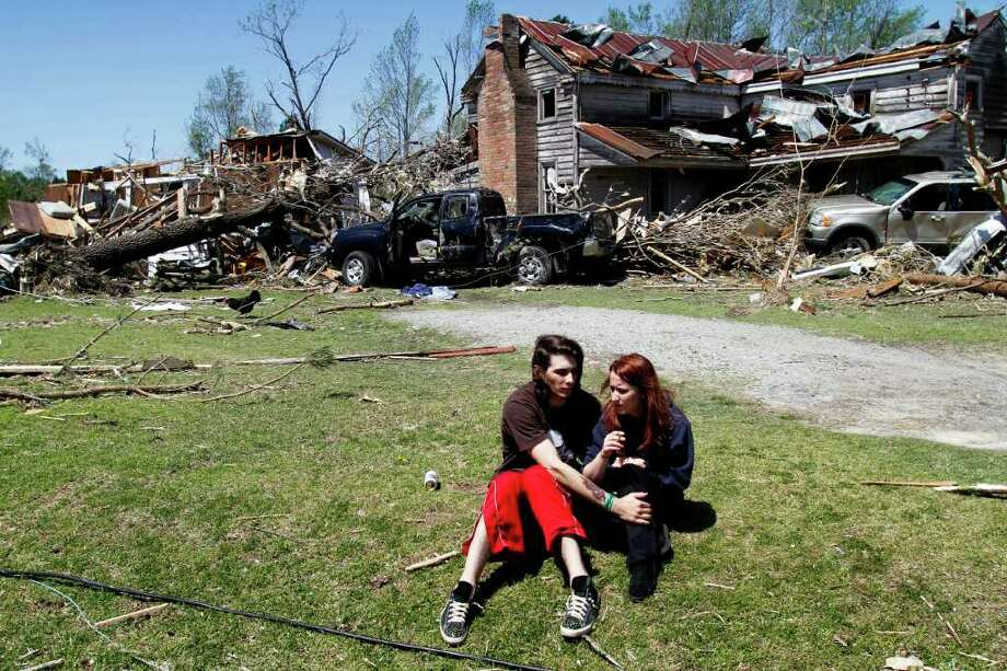 Nathaniel Ramey, left, comforts Megan Hurst at her grandmother's house in Askewville, N.C., Sunday, April 17, 2011 after a tornado struck Saturday. (AP Photo/Jim R. Bounds) Photo: Jim R. Bounds / FR3003 AP