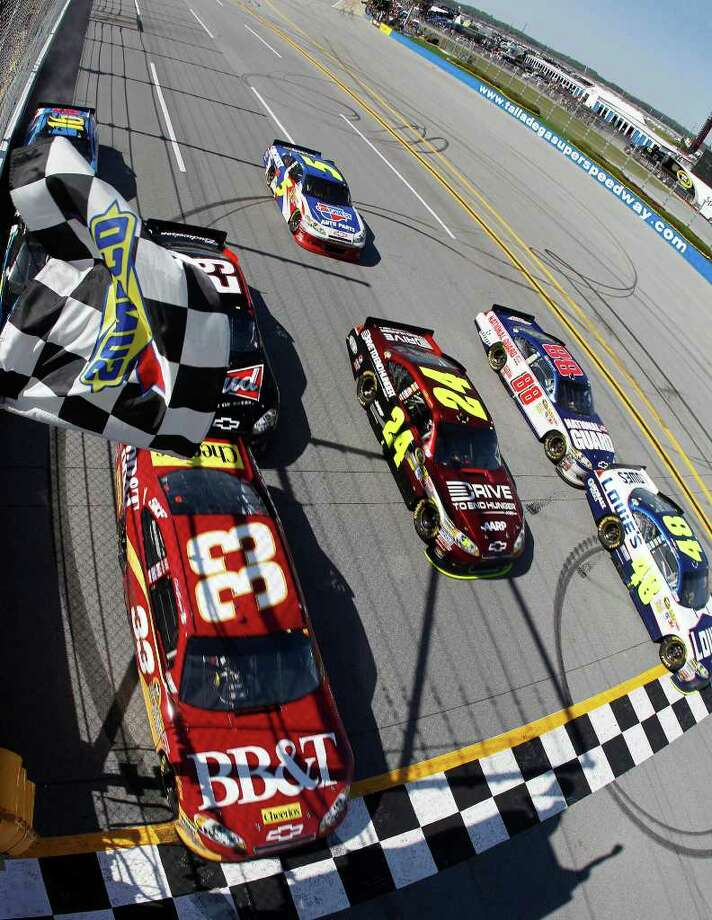 Jimmie Johnson (48) crosses the finish line slightly ahead of Clint Bowyer (33) to win the NASCAR Sprint Cup Series auto race at Talladega Superspeedway, Sunday, April 17, 2011, in Talladega, Ala. (AP Photo/Todd Warshaw, Pool) Photo: Todd Warshaw / 2011 Associated Press