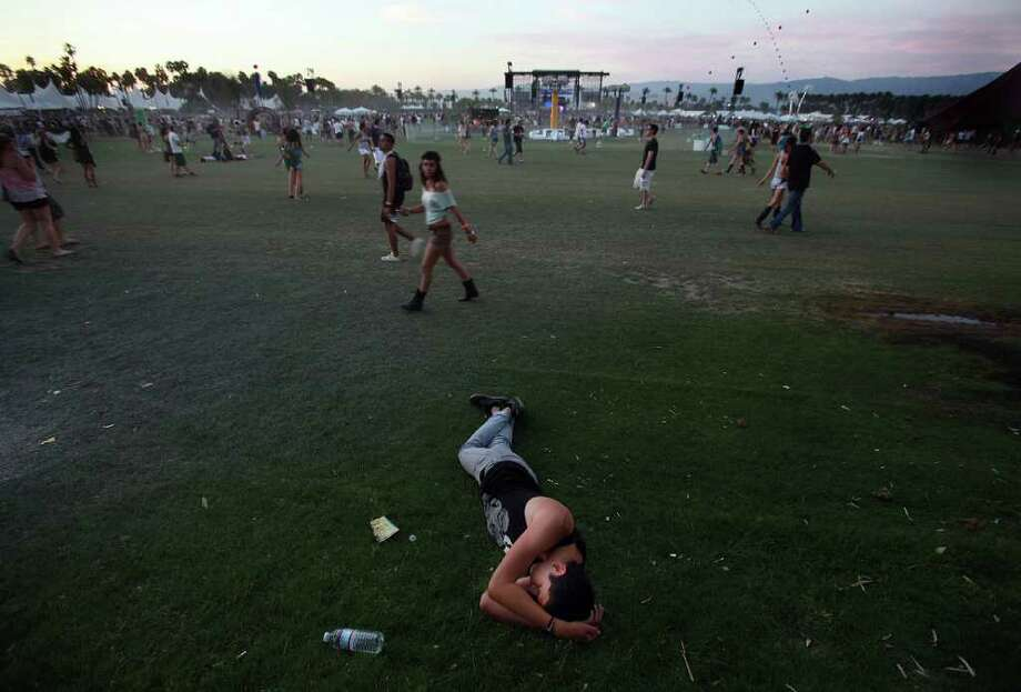 A tired fan naps as the sun sets on day 2 of the Coachella Valley Music and Arts Festival, Saturday, April 16 2011, in Indio, Calif. Photo: AP