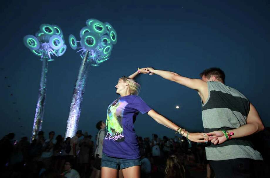 "Leah Cambell,20,left,  and Kyle Delilata dance under the art installation  ""Wish"", a 50 foot tall, 11 ton mixed media sculpture by Robert Buchholz at Coachella Valley Music and Arts Festival, Saturday, April 16 2011, in Indio, Calif. Photo: AP"