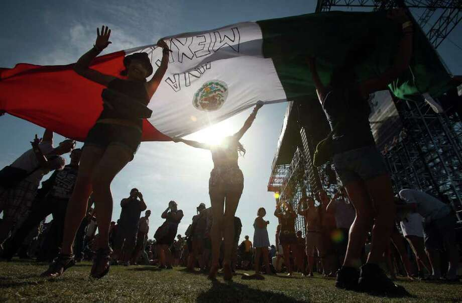 Fans wave a Mexican flag during Ozomatli performance at Coachella Valley Music and Arts Festival, Friday, April 15 2011, in Indio, Calif. Photo: AP