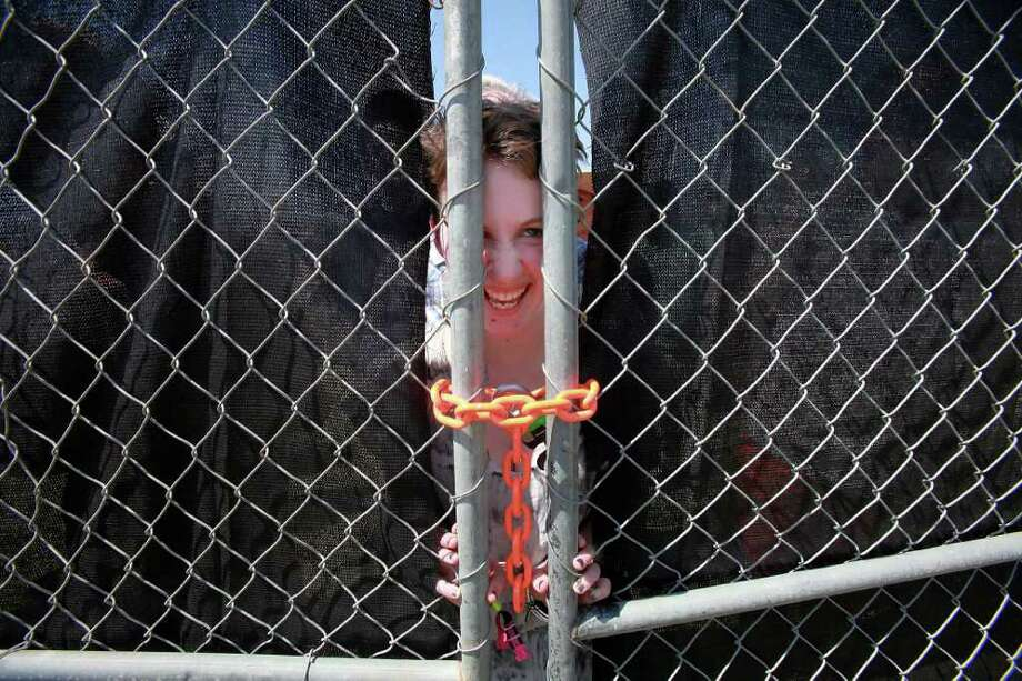 Cheyenne Sykes, 18, of Vancouver, Canada, waits behind a locked gate for the opening of the 12th Coachella Valley Music and Arts Festival, Friday, April 15 2011, in Indio, Calif. Photo: AP