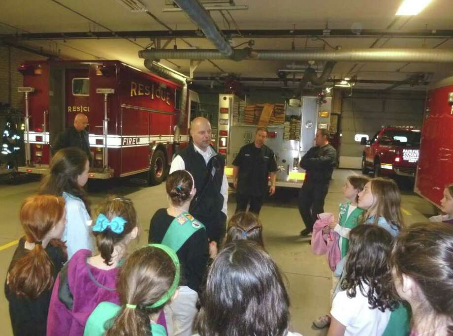 Assistant Fairfield Fire Chief George Gomola speaks with a group of Girl Scouts touring Fire Station 1 on Reef Road last week during Girl Scouts in Government Day. Photo: Contributed Photo/Mike Lauterborn / Fairfield Citizen contributed