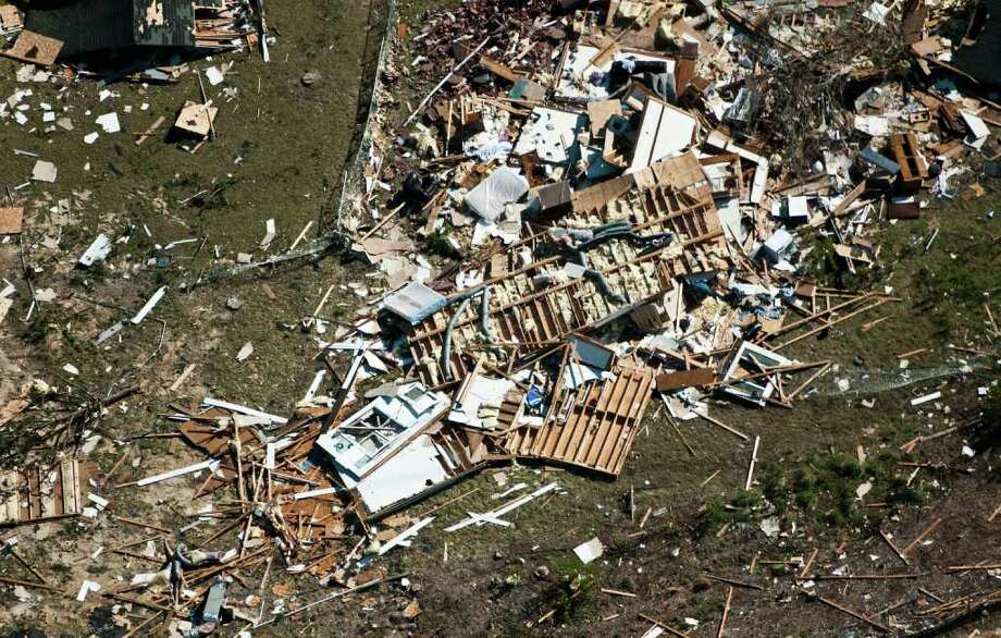 In this Sunday photo, a house lays in ruin in a subdivision in Fayetteville, N.C., after a tornado hit the area on Saturday. North Carolina Gov. Beverly Perdue plans to tour areas that were hit hard by a ferocious storm system with killer twisters that ripped through the South, killing at least 45 people across six states. (AP Photo/The Fayetteville Observer, Andrew Craft)  Photo: AP