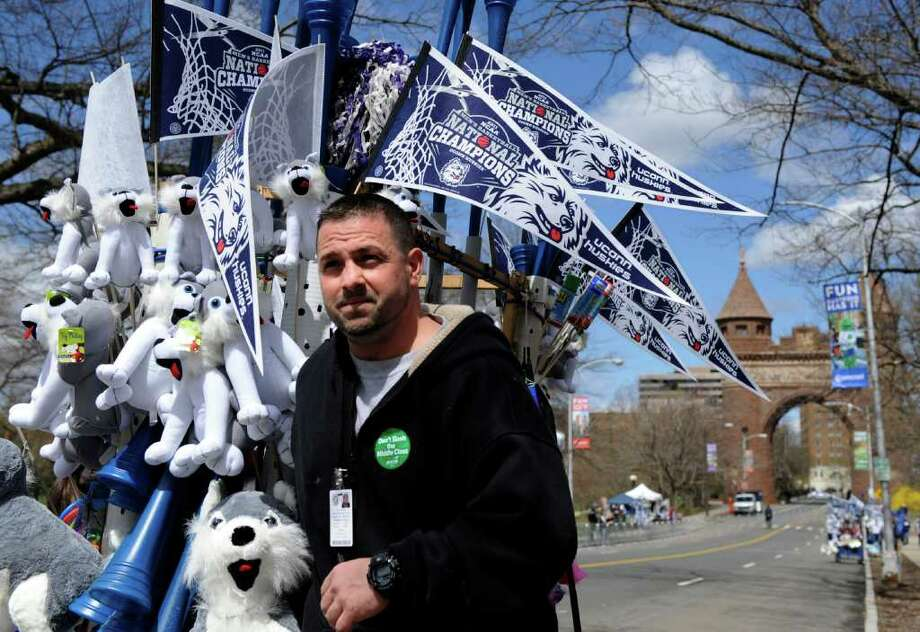 Alberto Paso, 31, of Derby prepares for a parade celebrating the Connecticut men's basketball team's national championship in Hartford, Conn., on Sunday, April 17, 2011. (AP Photo/Fred Beckham) Photo: Fred Beckham, AP / FR153656 AP