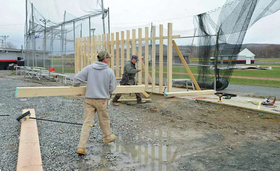 From left, David Krakat and Tommy Phibbs of Phibbs Contracting rebuild a dugout that was damaged due to high winds at the Brunswick Sports Complex in Brunswick, NY Monday April 18, 2011. (Lori Van Buren / Times Union) Photo: Lori Van Buren