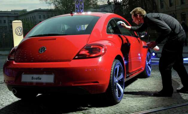 A man cleans the new Beetle car by the German car company Vokswagen after a news conference in Berlin Monday, April 18, 2011. In its 73-year history, the Beetle has evolved from the hippie ride of choice to a cute chick car. Now Volkswagen is reinventing it again. Photo: Michael Sohn, AP / AP